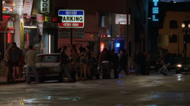 vídeos de stock, filmes e b-roll de tracking shot of black convertible with top down driving along street in red light district. many neon lights and sings lit, prostitutes walk up to car. - prostituta