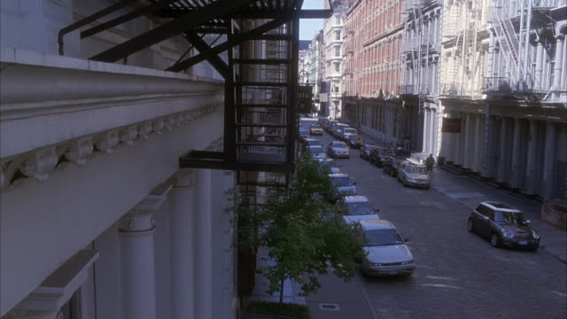 est wide angle on cars parked on small one way street viewed from a fire escape from a building. see apartment buildings across from shot. cars driving through row of parked cars. - one way stock videos & royalty-free footage