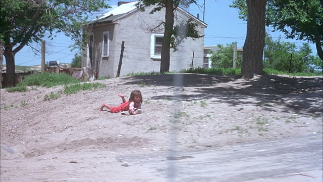 medium angle moving pov front passenger of car in reservation area with rundown houses. pass small girl laying on ground and american flag hung on one house. - native american reservation stock videos & royalty-free footage