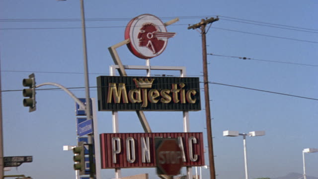 medium up angle driving pov passenger's side of town street in south central los angeles. sign of majestic car dealership and street sign reading crenshaw. - segnaletica stradale video stock e b–roll