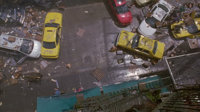 vídeos de stock, filmes e b-roll de high angle straight down from rooftop looking down on city street. see cars strewn all over street. people get out of cars and run away in panic or fear. debris falls onto ground. could be emergency or danger. chaos. pandemonium. - apavorado