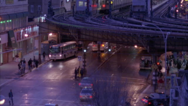 high angle down of elevated train tracks and intersection below. see cars drive and pass underneath tracks. see metro city buses at left. see people walking. - 1995年点の映像素材/bロール