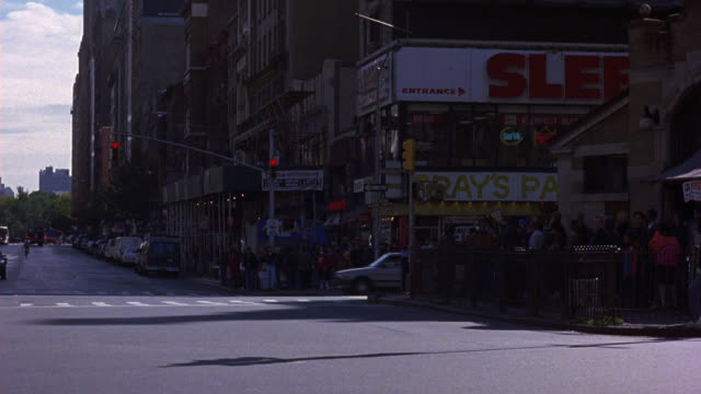 medium angle of  street intersection. see cars drive from frame right to frame left. see traffic light turn green. see a group of pedestrians on sidewalk frame right. see multi-level building containing stores. - level stock videos and b-roll footage