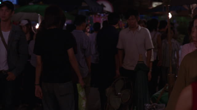 MEDIUM ANGLE OF CROWD IN MARKET. SEE PEOPLE WALKING PAST STREET VENDORS WITH LANTERNS. ASIA. ASIAN.