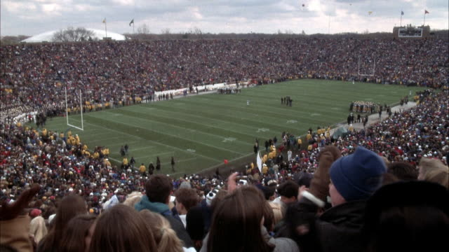vídeos de stock e filmes b-roll de pull back from football field with color guard to football stadium with cheering fans. color guard runs onto field, followed by university of notre dame football team. - futebol americano