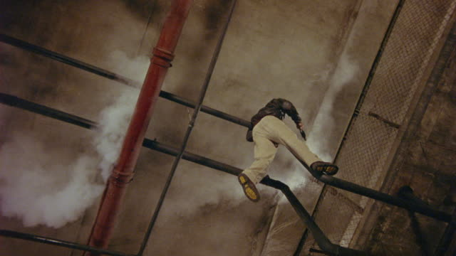 WIDE ANGLE OF MAN HANGING FROM METAL PIPE NEAR CEILING OF WAREHOUSE OR CONCRETE BUILDING. MAN HOLDS GUN AND FIRES IT ONCE AS HE FALLS. AN EXPLOSION OF SPARKS ILLUMINATES THE SCENE, AND SMOKE EMERGES FROM ABOVE. STUNTS.