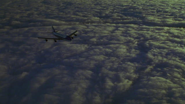 medium angle air force one flying across of clouds at dusk toward front right. - air force one stock videos & royalty-free footage