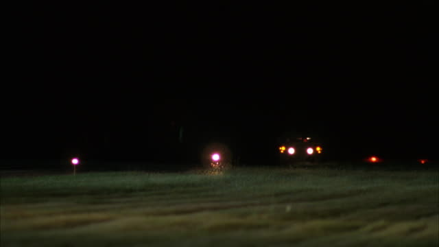 MEDIUM ANGLE OF LIT RUNWAY AT NIGHT. SEE JEEP ON RUNWAY. SEE AIR FORCE ONE AIRPLANE APPEAR FROM DISTANCE, AIRPLANE DESCENDS AND LANDS. SEE JEEP GUIDING IN FRONT OF AIRPLANE ON RUNWAY. CLOSE UP OF AIRPLANE WHEELS AS AIRPLANE EXITS FRAME TO LEFT.
