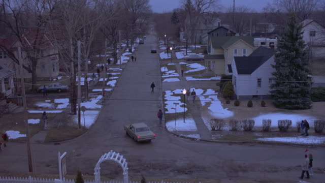 vídeos de stock e filmes b-roll de wide angle of middle class suburban neighborhood. t road with some people walking and two story houses and bare trees on sides. - 1993