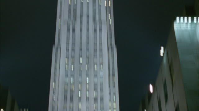 medium angle of rockefeller center building with lit christmas tree in front. continues to pan up and down over building and christmas tree below. - rockefeller center video stock e b–roll