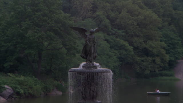 vídeos y material grabado en eventos de stock de medium angle of water fountain in central park. see angel statue on top of fountain. see people walking and sitting around fountain. see pond or lake in background. may be bethesda terrace and angel of the waters fountain. - fuente bethesda