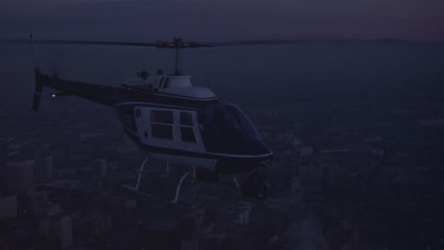medium angle of police helicopter flying right, by downtown los angeles skyscrapers of first interstate bank and croker bank. helicopter approaches sunset with hues of pink and purple in far background. - american interstate stock videos & royalty-free footage