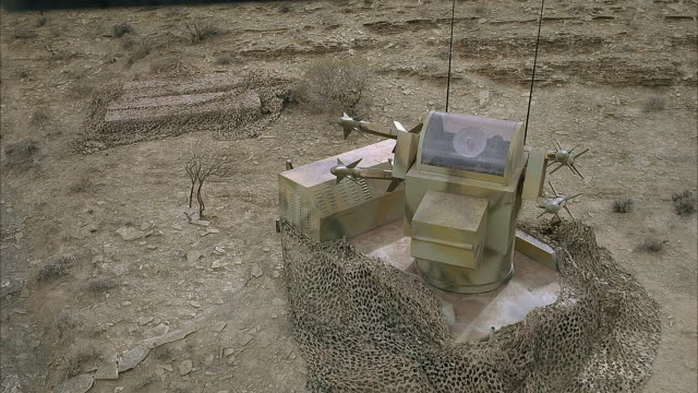 high angle down angle of missile launcher with four missiles or rockets surrounded by camouflage netting. see desert environment, barren ground. missile launcher appears to have small radar dish on top center. - radar bildbanksvideor och videomaterial från bakom kulisserna