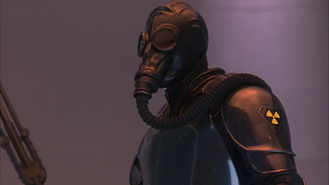 medium angle of uniformed soldier in black radiation suit with gas mask holding weapon. weapon could be futuristic sword. see soldier attempt to block off screen attacker. - suit of armor stock videos and b-roll footage