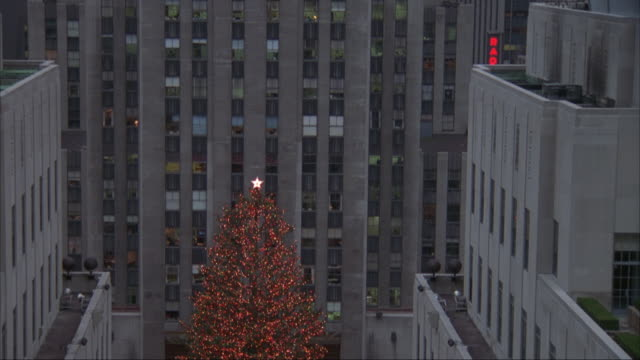 pan down from rockefeller center building to lit christmas tree below. see office buildings on either side of tree. then see people skating on ice rink below. see heralding angeles with trumpets in front. see several people milling around. - rockefeller center video stock e b–roll