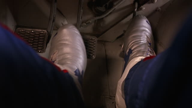 CLOSE ANGLE OF MAN'S FEET PUSHING PEDALS IN CAR OR RACE CAR. FEET PRESS ON GAS, CLUTCH AND BRAKE SEVERAL TIMES BEFORE BOTH FEET PUSH ON BRAKE AT END OF CLIP AS IF ABOUT TO CRASH.