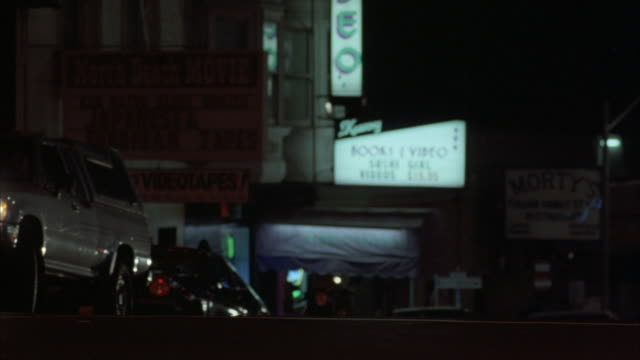 TRACKING SHOT OF COUPLE WALKING FROM LEFT TO RIGHT TOWARDS RED LIGHT DISTRICT OR STRIP CLUB, SIGNS READ XXX RATED VIDEO MOVIE ARCADE AND LUSTY LADY THEATRE - LIVE NUDES AND MOVIES.
