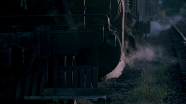 close up shot of steam engine train arriving at train depot. shot begins on front of train, tilts down, revealing side of train and railroad tracks. steam seen venting from train's lower carriage area. - steam stock videos & royalty-free footage