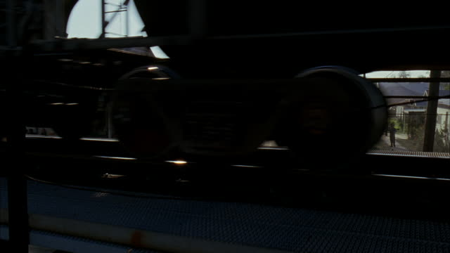 pan down a train trestle as a locomotive passes over the rusted steal beams.  a few period cars parked on the side of the road next to early 1900s wood houses and buildings. railroads, railroad tracks, tracks, beams, rust. - next to stock videos and b-roll footage