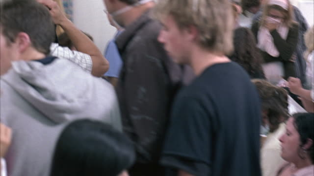 stockvideo's en b-roll-footage met medium angle of nurses, men and women in crowded hospital triage area, people coughing, covering mouths with face masks. clinics, medical centers, patients. could be emergency room. - triage