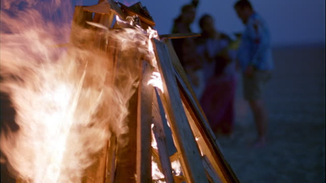 close angle of bonfire on beach. fire consists of long pieces of wood arranged in pyramid shape. three people can be seen standing on beach in background. one person dancing. wind blows flames of fire. could be beach party. - bonfire stock videos & royalty-free footage