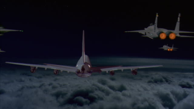 medium angle of rear of air force one in sky flying over clouds, two air force jets on each side escort air force one. jets bank to right top and exit screen. pans up, bottom rear of c-130 hercules airplane appears from top. - anno 1997 video stock e b–roll