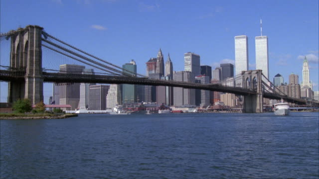wide angle of brooklyn bridge with new york city skyline in background. see world trade center twin towers in background. boat passes under bridge and exits on right. another boat starts on right and moves toward camera. - brooklyn bridge stock videos & royalty-free footage