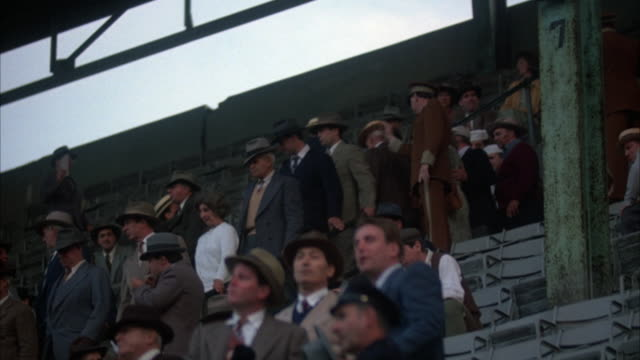 BASEBALL STADIUM CROWD, MOSTLY MALES DRESSED IN 1940'S PERIOD ATTIRE, ENTERING SEATING AREA. AN USHER, IN FULL UNIFORM, IS SEEN AMONGST THE CROWD. CLOUDS OR SMOKE IS SEEN MOVING IN BACKGROUND SKY AREA.