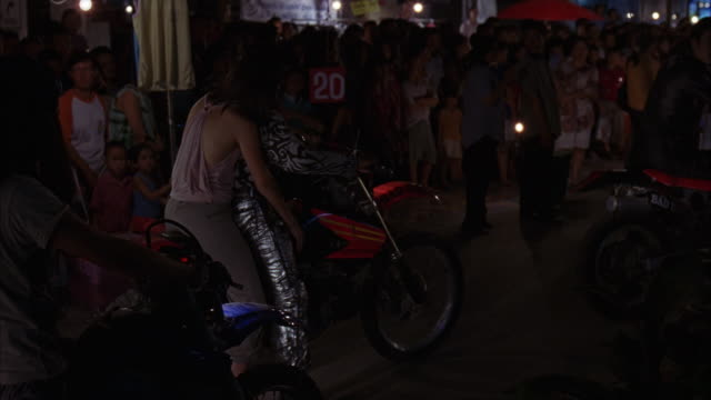 vidéos et rushes de tracking shot of people riding motorcycles through market or marketplace. see gang pass crowd. could be dirt bikes and part of chase past street vendors. - groupe organisé