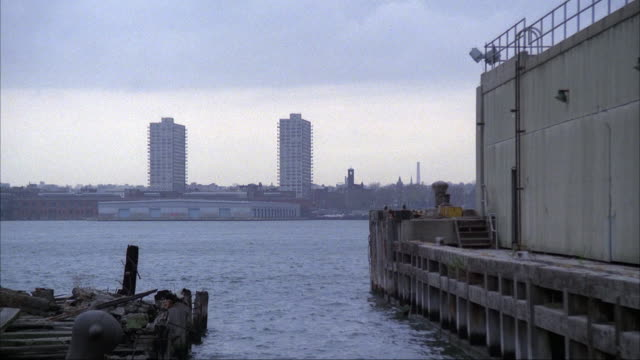 medium angle of hudson river facing new jersey in background, two tall buildings and industrial area. boat dock and building in foreground. - pråm bildbanksvideor och videomaterial från bakom kulisserna