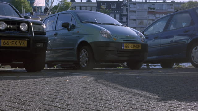 MEDIUM ANGLE OF BLUE HATCHBACK PARKED ON SIDE OF STREET. BLACK CAR OR VOLKSWAGEN APPEARS FROM LEFT AND QUICKLY PASSES TO RIGHT SWERVING AS IT CROSSES BRIDGE. MAN WEARING PINK SHIRT PASSES TO LEFT, BICYCLE IN RIGHT FOREGROUND.