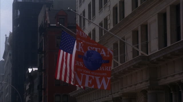 wide angle on an american flag and an orange flag that reads new york standing hanging off the side of a building. - awning stock videos and b-roll footage