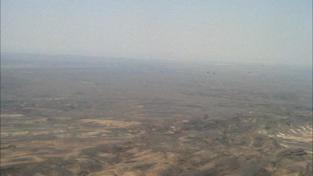 tracking shot of two camouflage f-16 fighter jet flying at far distance. see jets approach side by side  fly until off screen. then see two jets enter from right and fly towards left. neg cut. middle east. - fighter stock videos & royalty-free footage