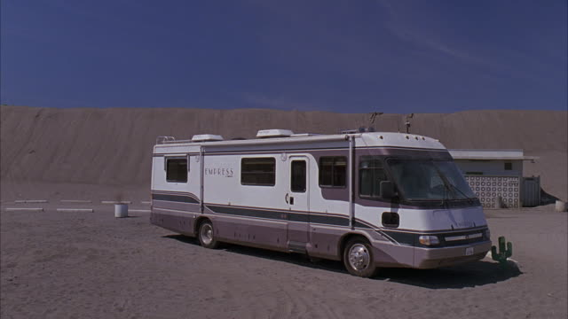 wide angle of desert parking lot. could be for campground or national park. rvs, campers parked near one story building. could be trailer park. - trailer stock videos & royalty-free footage