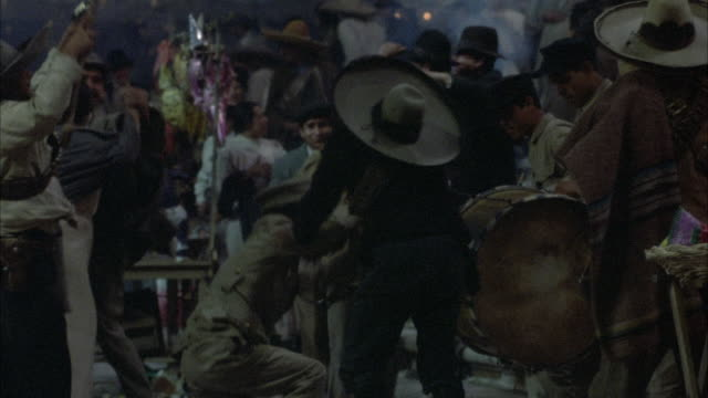 MEDIUM ANGLE OF CELEBRATION, FESTIVAL OR FIESTA. MEN WAVE GUNS IN CELEBRATION. SEE MEN BEATING UP MAN AND HOLDING A GUN TO HIS HEAD. PEOPLE DANCING. BRASS BANDIN RIGHT BACKGROUND. SPARKS FROM FIREWORKS IN BACKGROUND. ACTION.