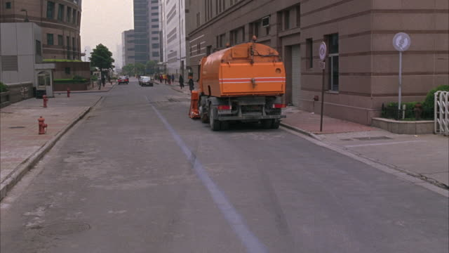 MEDIUM ANGLE OF DOWNTOWN CITY STREET, OR ALLEY. SEE PEDESTRIANS ON SIDEWALKS OF BOTH FRAMES IN BACKGROUND. SEE LARGE ORANGE BIOHAZARD OR GARBAGE TRUCK PARKED IN FOREGROUND RIGHT.