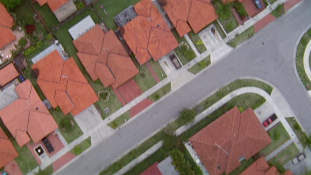 aerial birdseye pov of rooftops of rows of houses in tract housing community. see houses curve along path of streets. - tract housing stock videos and b-roll footage