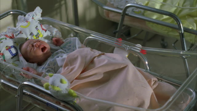 MEDIUM ANGLE OF A BABY GIRL LAYING IN A HOSPITAL BASSINET. SEE BABY FUSSING, CRYING AND WAVING ARMS IN AIR. SEE BABY COVERED BY A PINK BLANKET WITH A WHITE AND YELLOW STUFFED BEAR AT HER SIDE. HOSPITAL MATERNITY WARD. NEWBORNS.