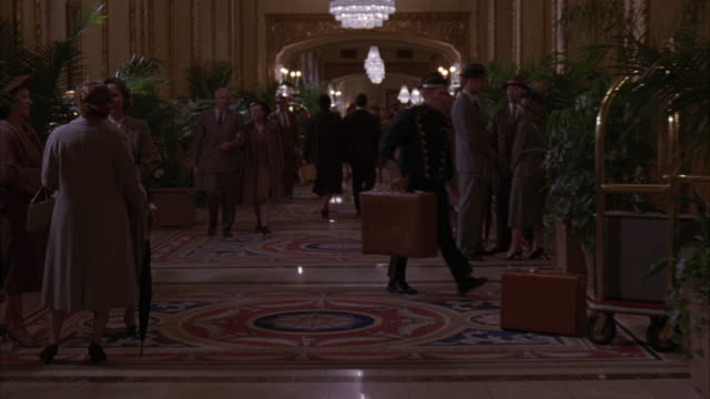 MEDIUM ANGLE OF A DOLLY THROUGH A 1950'S HOTEL LOBBY, FILLED WITH PLANTS, FERNS, AND PEOPLE DRESSED IN FANCY UPSCALE PERIOD CLOTHES. THE MEN WEAR THREE PIECE SUITS WITH OVERCOATS AND HATS, AND THE WOMEN WEAR FORMAL BUSINESS SKIRTS AND DRESSES.