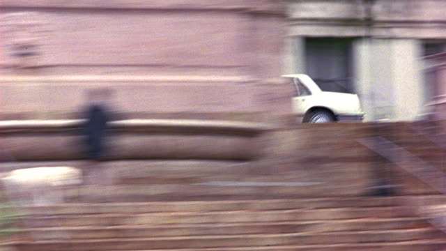 TRACKING SHOT OF WHITE, FOUR DOOR 1980'S SEDAN, CAR, OR VEHICLE TRAVELING OR DRIVING ON CITY STREETS NEAR VARIOUS APARTMENT BUILDINGS AND MULTI-STORY BUILDINGS. COULD BE MERCEDES. SEE VARIOUS GREEN BUSHES, TREES, OR LEAVES PASS IN FRAME.