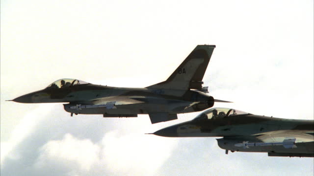 vídeos de stock e filmes b-roll de tracking shot of two camouflage f-16 jet fighters flying. flying pov from left side of jets. jets appear to be flying backwards as pov is traveling faster. see clouds. - avião de combate
