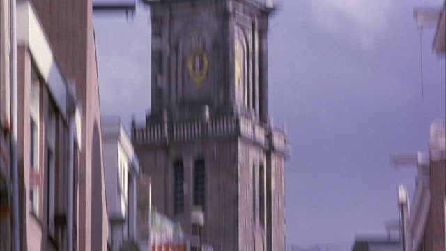pan down of cathedral spire. clock on cathedral reads six o' clock. pov pans down to show spire then back up to show top. pov pans down again to show street below. see multi-story buildings, bicycles parked below. - spire stock videos & royalty-free footage