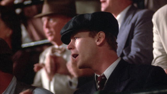 vídeos de stock, filmes e b-roll de series of close angle shots of male spectators, at baseball stadium, dressed in 1940's attire.  focus on facial expressions of men, engaged in action occurring off screen. - 1940