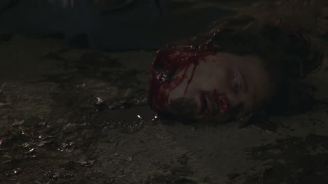 vídeos de stock e filmes b-roll de medium angle of severed bloody human head in dirt. decapitation and death could be from murder. puddle of water and blood under head. eyes are slightly open. head has brown hair and facial hair. head is part of corpse or dead body. gore. - matar