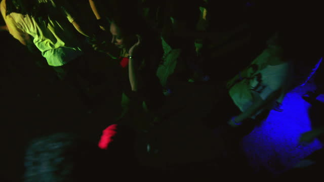 high angle down of a crowd of college age men and women, probably students.  could be a party, rave, dance club, concert, disco, or discotheque. the students look into the camera as it goes up and down. - infestation stock videos & royalty-free footage