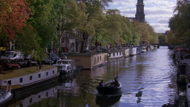 vídeos de stock e filmes b-roll de pan up of canal. see houseboats, trees lining canal, cars driving along side. see small boat with two passengers travel towards pov. pov pans up to show length of canal and bridge. see top of cathedral in background. - barco casa