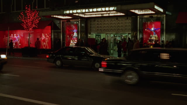 medium angle of bloomingdale's department store entrance, pov from across city street in downtown. pedestrians walk by, taxis and traffic in front of entrance. - 1995年点の映像素材/bロール