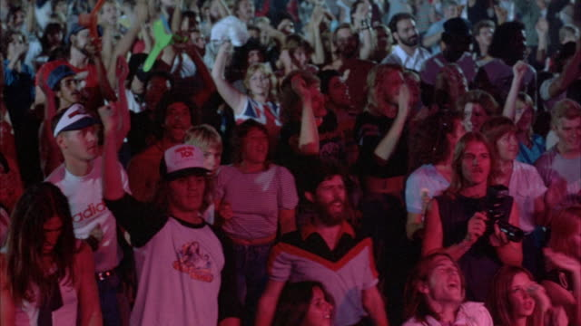 MEDIUM SHOT OF MULTIPLE PANS R-L AND L-R ACROSS ROCK CONCERT AUDIENCE (YOUNG AND DRESSED IN EARLY 1980'S ATTIRE). CROWD START IN THEIR SEATS BUT BEGIN TO ROCK BACK AND FORTH, OCCASIONALLY RAISING THEIR ARMS.