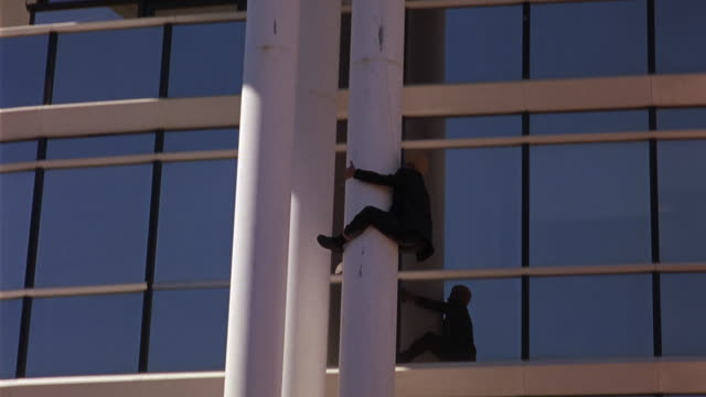 TRACKING SHOT OF MAN ATTACHED TO CABLE SLIDING DOWN WHITE STEEL SUPPORT COLUMN OF MODERN OFFICE BUILDING. TURNS UPSIDE DOWN PULLS OUT GUN AND FIRES UPWARD. TURNS RIGHT SIDE UP. GLASS WINDOWS REFLECT SURROUNDING BUILDINGS. GUNFIRE.