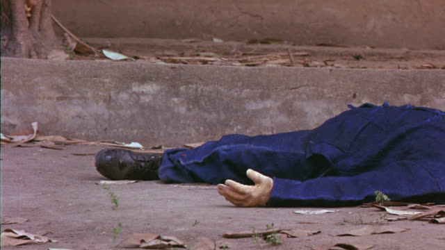 MEDIUM ANGLE OF MAN IN BLUE COVERALLS LYING IN STREET.  SPARK IGNITES, MAN DRAGGED KICKING AND FLAILING THROUGH LEAVES ON STREET. SPARK MIGHT BE FROM GUNFIRE. STUNT.